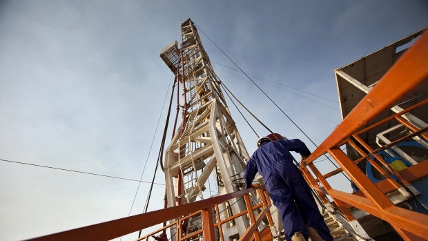 A worker for the Chinese company Zhongyuan Petroleum Exploration Bureau (ZPEB) climbs onto the drilling platform of an oilrig near Melut, in the Upper Nile, Sudan, on Monday, Nov. 29, 2010.
