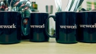 Cutlery stands in WeWork Cos. branded mugs in a kitchen area in the WeWork Cos. co-working space at the One Poultry building in the City of London, U.K., on Wednesday, Oct. 3, 2018. Hana Financial Group Inc. is in talks to buy the building, best known for its stripes of pink and yellow limestone, that has been transformed into a major WeWork Cos. co-working space.