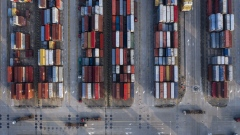 Trucks move past containers stacked at the Yangshan Deepwater Port, operated by Shanghai International Port Group Co. (SIPG), in this aerial photograph taken in Shanghai, China, on Wednesday, Aug. 7, 2019. Trump's threat to raise tariffs on all Chinese goods last week shattered a truce reached with Xi just weeks earlier, unleashing tit-for-tat actions on trade and currency policy that risk accelerating a wider geopolitical fight between the world's biggest economies.