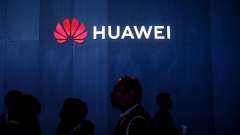 An illuminated logo hangs above the Huawei Technologies Co. pavilion on the opening day of the MWC Barcelona in Barcelona.