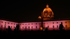 People are silhouetted as the North Block of the Central Secretariat buildings, which houses the Ministries of Finance and Home Affairs, stands illuminated at night in New Delhi, India, on Sunday, Jan. 28, 2018. With India's Finance Minister Arun Jaitley readying to deliver his annual budget on Feb. 1, traders are seeking to hedge a rally that has added more than $425 billion in equity values in the past four months.