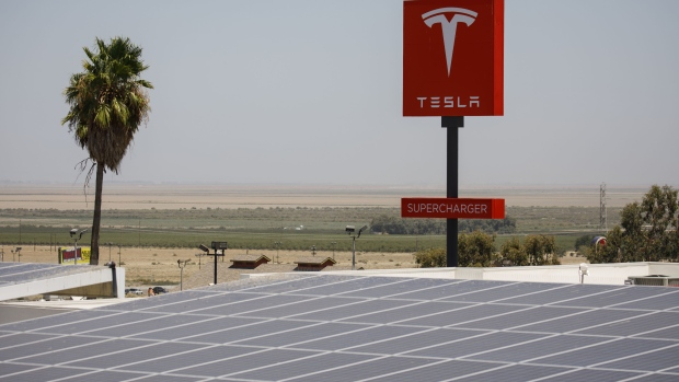 Signage is displayed near a solar panel next to the entrance of the new Tesla Inc. showroom in New York, U.S., on Thursday, Dec. 14, 2017. The Meatpacking District location, which opens to the public at 11 a.m. Friday, lets customers for the first time explore energy offerings, configure and place orders all under one roof.
