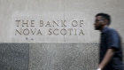 A pedestrian passes in front of a building displaying The Bank of Nova Scotia (Scotiabank) signage in the financial district of Toronto, Ontario, Canada, on Thursday, July 25, 2019. Canadian stocks fell as tech heavyweight Shopify Inc. weighed on the benchmark and investors continued to flee pot companies.