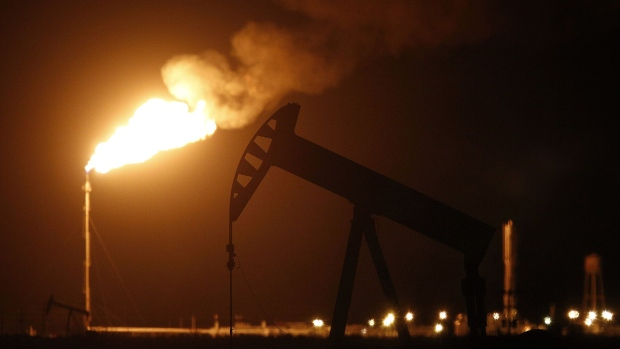 The silhouette of an electric oil pump jack is seen near a flare at night in the oil fields surrounding Midland, Texas.