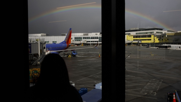 A passenger looks out as a Southwest Airlines Co. Boeing Co. 737-700 jet aircraft stands on the tarmac beneath a rainbow at San Francisco International Airport (SFO) in San Francisco, California, U.S., on Wednesday, March 27, 2019. The ban on Boeing 737 Max flights plus soft leisure-travel demand will shave $150 million from Southwest's first-quarter revenue.