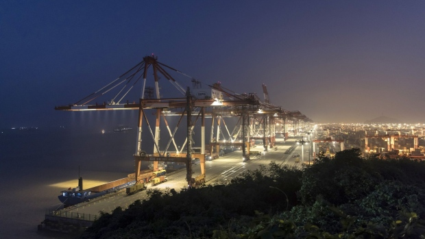 Trucks drive past gantry cranes at the Yangshan Deepwater Port, operated by Shanghai International Port Group Co. (SIPG), in the early morning in Shanghai, China, on Wednesday, Aug. 7, 2019. Trump's threat to raise tariffs on all Chinese goods last week shattered a truce reached with Xi just weeks earlier, unleashing tit-for-tat actions on trade and currency policy that risk accelerating a wider geopolitical fight between the world's biggest economies.