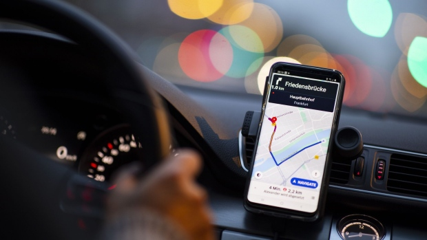 A dashboard-mounted smartphone displays the Uber app in Frankfurt, Germany.