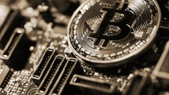 A coin representing Bitcoin cryptocurrency sits on a computer circuit board in this arranged photograph in London, U.K., on Tuesday, Feb. 6, 2018. Cryptocurrencies tracked by Coinmarketcap.com have lost more than $500 billion of market value since early January as governments clamped down, credit-card issuers halted purchases and investors grew increasingly concerned that last years meteoric rise in digital assets was unjustified.