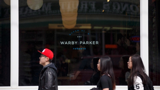 People walk by U.S. based eyewear boutique Warby Parker's flagship Toronto store on Queen St., in To