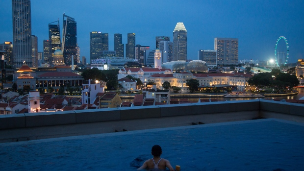 A woman looks towards the city skyline from a swimming pool at dusk in Singapore, on Tuesday, July 11, 2017. Singapore is scheduled to release second-quarter gross domestic product data on July 14.