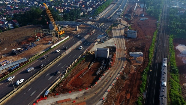 A crane stands at a construction site as vehicles travel along the Jakarta-Serpong Toll Road in this aerial photograph taken in Jakarta, Indonesia, on Friday, Feb. 1, 2019. Indonesia is scheduled to release fourth-quarter gross domestic product (GDP) figures on Feb. 6.