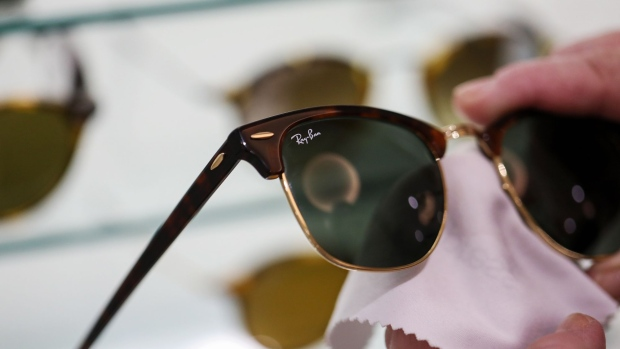 A employee cleans a pair of Ray-Ban Clubmaster luxury sunglasses, manufactured by Luxottica Group SpA, in an opticians in London, U.K., on Monday, Jan. 16, 2017. French lensmaker Essilor International SA agreed to buy Luxottica Group SpA, the maker of Ray-Ban sunglasses, for about 22.8 billion euros ($24 billion) in stock, combining the largest manufacturer and retailer in eyewear.