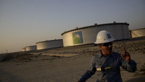 An employee walks past crude oil storage tanks at the Juaymah Tank Farm in Saudi Aramco's Ras Tanura oil refinery and oil terminal in Ras Tanura, Saudi Arabia, on Monday, Oct. 1, 2018. Saudi Arabia is seeking to transform its crude-dependent economy by developing new industries, and is pushing into petrochemicals as a way to earn more from its energy deposits.