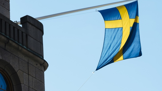 A national flag of Sweden hangs from a commercial building in Stockholm, Sweden.
