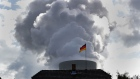 A German national flag flies in front of coal emissions in Spremberg. Photographer: Krisztian Bocsi/Bloomberg