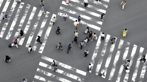 Pedestrians cross an intersection in Tokyo, Japan, on Tuesday, July 9, 2019. Japan's wages dropped for a fifth month, according to Japan's Ministry of Health, Labour and Welfare, adding to concerns over the resilience of consumer spending as a sales tax increase approaches in October.