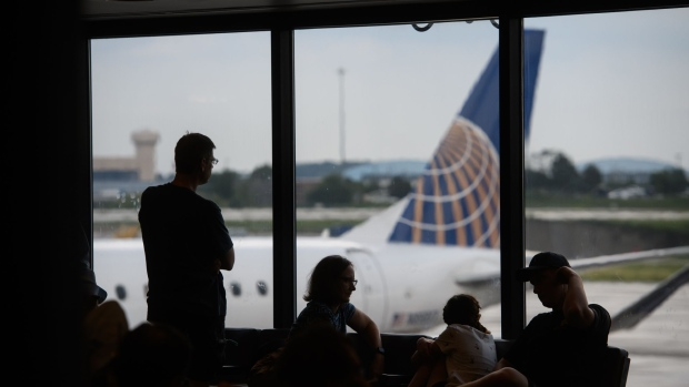 People watch as a United Airlines Holdings Inc. plane arrives at a gate at the Pittsburgh International Airport (PIT) in Moon Township, Pennsylvania, U.S., on Tuesday, July 2, 2019. Programs adopted or being considered by a number of airports allow people beyond security checkpoints so they can meet arriving relatives or just hang out as airports expand options to fill passenger dwell time.