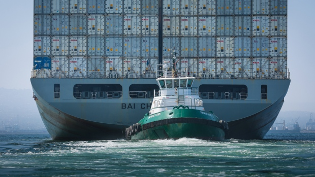 A tugboat guides the Kawasaki Kisen Kaisha Ltd. Bai Chay Bridge cargo ship into the Port of Long Beach in Long Beach, California, U.S., on Wednesday, April 4, 2018.