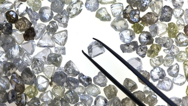 An uncut diamond is selected from a collection of colorless and colored diamonds on a sorting table at DTC Botswana, a unit of De Beers, in Gaborone, Botswana.