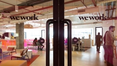 Signage is displayed on glass doors at a WeWork co-working space in Gurugram, India.