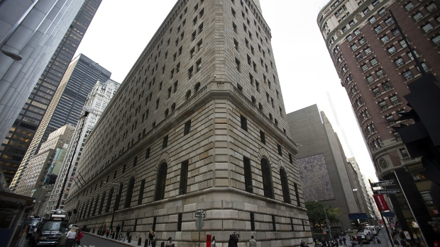 Pedestrians walk past the New York Federal Reserve building in New York, U.S., on Wednesday, Oct. 17, 2012.
