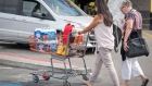 A customer pushes a shopping cart with bottled water, flashlights, and batteries in a Home Depot