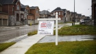 "A ""For Sale"" sign stands in front of homes in East Gwillimbury, Ontario, Nov. 2, 2018."
