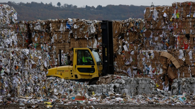 A forklift truck driver moves bales of recycled cardboard at a paper mill in the U.K. Photographer: Luke MacGregor/Bloomberg