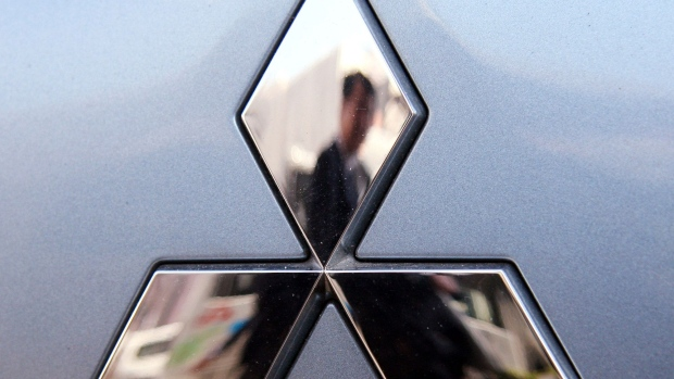 JAPAN - MARCH 11: A man is reflected in the Mitsubishi Motors Corp. logo at the company's headquarters in Tokyo, Japan, on Tuesday, March 11, 2008.