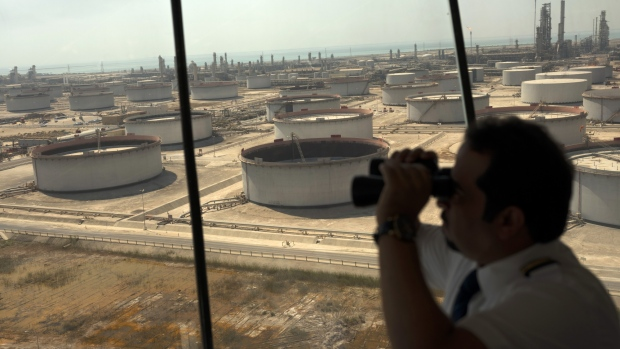 An employee uses binoculars to look out towards the Arabian Sea in the Port Control Center at Saudi Aramco's Ras Tanura oil refinery and terminal in Ras Tanura, Saudi Arabia, on Monday, Oct. 1, 2018.