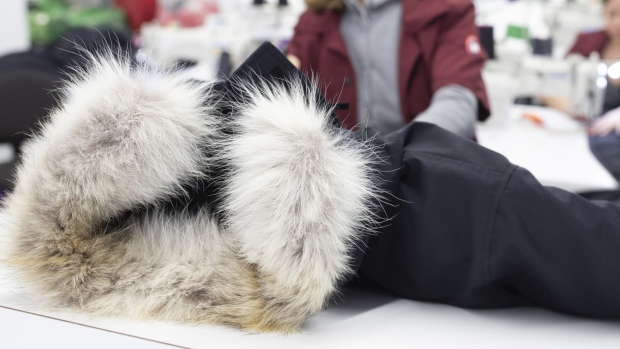 An employee checks a finished jacket with a fur collar at the new Canada Goose Inc. manufacturing fa