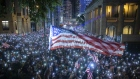 Demonstrators wave U.S. flags during a rally in support of the Hong Kong Human Rights and Democracy Act, Oct. 14.