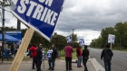 Demonstrators hold signs during a United Auto Workers strike outside the GM plant in Romulus, Michigan on Oct. 4.