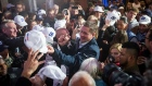 Andrew Scheer, leader of the Conservative Party, centre, signs an autograph on a baseball cap during
