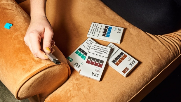 A person holds a Juul Labs Inc. e-cigarette next to packages of flavored pods in this arranged photograph taken in the Brooklyn Borough of New York, U.S., on Thursday, Dec. 20,