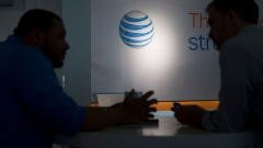 The AT&T Inc. logo is seen past a customer and a retail sales consultant at an AT&T store in Washington, D.C., U.S., on Tuesday, April 21, 2015.