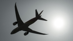 A plane is silhouetted as it takes off from Vancouver International Airport in Richmond, B.C.