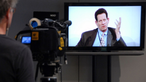 A cameraman films a television monitor showing Kenneth Fisher, chief executive officer of Fisher