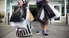 Shoppers hold retail bags in an arranged photograph at Yorkdale mall in Toronto, Ontario, Aug. 22, 2