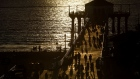 People walk on the pier at sunset in Manhattan Beach, California, U.S.