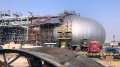 Scaffolding surrounds a primary-separation spheroid at Saudi Aramco's crude oil processing facility
