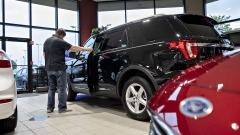 A customer looks over a Ford 2020 Explorer on display at a car dealership in Orland Park, Illinois. Photographer: Daniel Acker/Bloomberg