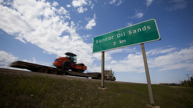 A truck drives past a Suncor Energy Inc. Energy Inc. oil sands road sign near Fort McMurray, Alberta