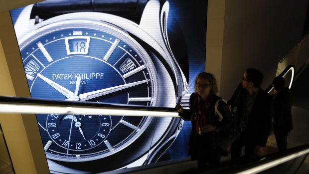 Visitors traveling on an escalator pass a Patek Philippe SA luxury wristwatch advertisement during the opening day of the 2018 Baselworld luxury watch and jewelry fair in Basel, Switzerland, on Wednesday, March 21, 2018. Swiss watch exports kicked off 2018 with the strongest growth in more than five years, buoyed by strong demand for high-end timepieces in Asia and a later Chinese New Year.