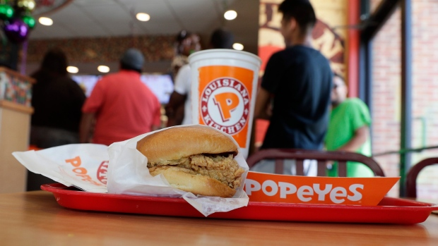 A chicken sandwich sits on a table at a Popeyes as guests wait in line, Aug. 22, 2019, in Kyle, Texa