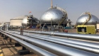 Three-phase spheroids stand behind pipelines at Saudi Aramco's crude oil processing facility