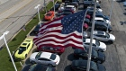 An American flag flies above General Motors Co. vehicles displayed at a car dealership in this aeria