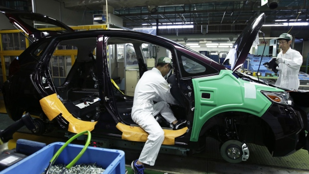 Workers assemble a Honda Motor Co. North America-bound Fit vehicle on the production line at the company's Suzuka factory in Suzuka, Mie, Japan, on Tuesday, Aug. 23, 2016. Attracting the best information technologists is becoming increasingly important for Honda Motor Co. and other carmakers as they seek a bigger share of revenue from IT-driven services such as ride-sharing and cloud-based monitoring of vehicles.