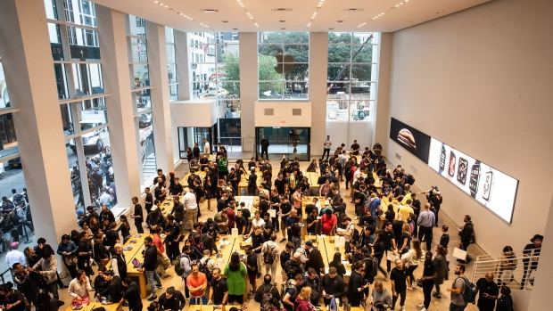 Employees assist customers with Apple Inc. products during a sales launch at a store in New York.