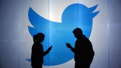 People are seen as silhouettes as they check mobile devices whilst standing against an illuminated wall bearing Twitter Inc.'s logo in this arranged photograph in London, U.K., on Tuesday, Jan. 5, 2016. Twitter Inc. may be preparing to raise its character limit for tweets to the thousands from the current 140, a person with knowledge of the matter said.